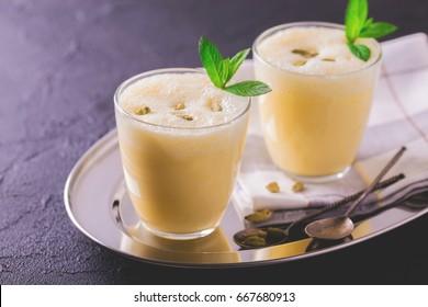 Traditional Indian mango lassi curd with cardamon, mint, vanilla and saffron served in terracotta glasses. Kesariya. Keshariya. Kesar. Yogurt smoothie