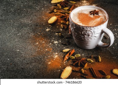 Traditional indian masala chai tea with spices - cinnamon, cardamom, anise, dark stone background. Copy space