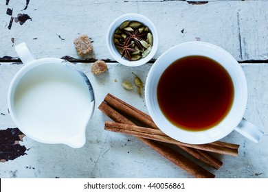 Traditional Indian masala tea with spices (cinnamon, anise, cardamom, sugar) over old wooden background in white ceramic cup, top view.