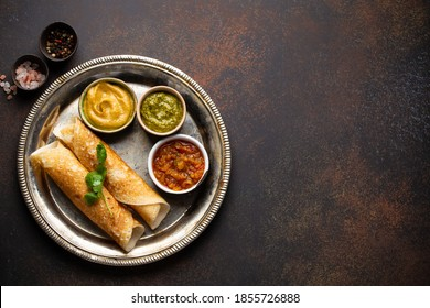 Traditional Indian rice pancakes Dosa with different dips chutney, on rustic metal plate on dark brown stone background table. Quick meal or vegetarian snack of South India, top view, space for text
