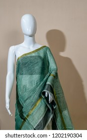 A traditional Indian silk saree displayed for sale on mannequin dressmaker model on isolated Vertical background.