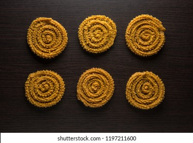 Traditional Indian snack - Chakli or Murukku placed in a row on dark background. Indian authentic and regional food and recipes. View from above.