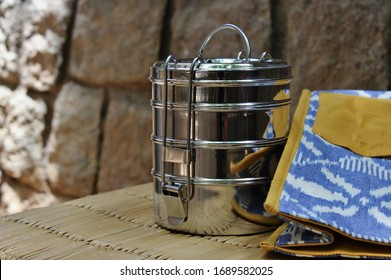 Traditional Indian steel lunchbox and ikat fabric bag against a stone background