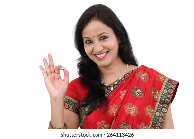 Traditional Indian Young woman making OK sign against white background