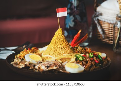 Traditional Indonesian Cuisine Nasi Tumpeng for Independence Celebration with Flag. Tumpeng is a cone-shaped rice dish like mountain with meats usually eat as breakfast or lunch