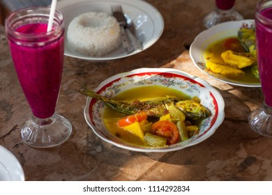 Traditional Indonesian fish curry with rice and dragonfruit juice