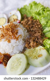 Traditional Indonesian food consist of rice, cucumber, fried onion, lettuce, chicken chop meat and egg in close up view