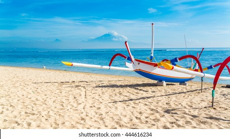 A traditional Indonesian outrigger canoe still used for day to day fishing by locals sits on the beach on a beautiful blue sky day.