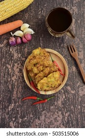 Traditional Indonesian Snack, Bakwan, vegetable fritter made from corn, carrot and cabbage served with red chili on wooden background