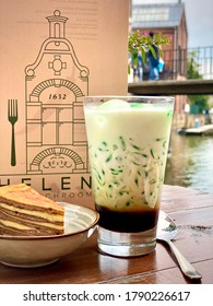 Traditional Indonesian sweet refreshing drink cendol made from pandas juice, mung bean. Restaurant cafe wooden table outside outdoors. Served drink in glass with a slice of layer cake in a bowl with a