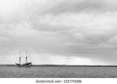 Traditional Indonesian wooden sailboat with gathering storm clouds in the background.