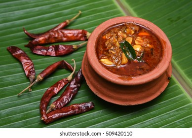 Traditional Injipuli/Puli inji is dark brown Kerala cuisine made of ginger Tamil Nadu, Kerala in South India served for Onam sadhya, Vishu. hot, sweet and sour ginger pickle in clay pot. Indian spices