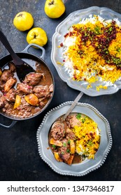 Traditional Iranian khoresh beh stew with chunks of lamb, quinces and saffron rice as top view in a cast-iron roasting dish and pewter plate