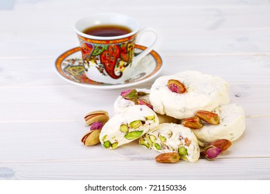 Traditional Iranian and Persian pieces of white nougat dessert sweet candies (Gaz) with Pistachio nuts from Isfahan City and a cup of tea on white wooden background