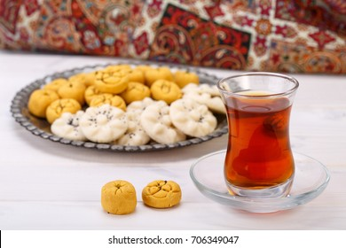 Traditional Iranian Sweets Round shaped Chickpea cookie pastries and rice cookies in Persian Toreutic plate with a close up shot of glass cup and saucer tea on white wooden background