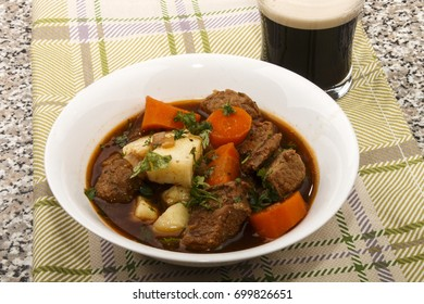 traditional irish beef and guinness beer stew with carrots and fresh parsley in a plate