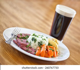 Traditional Irish St. Patricks Day meal of corned beef, potatoes and carrots and a stout beer