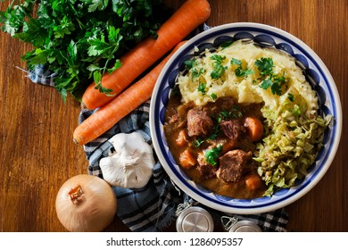 Traditional irish stew served with mashed potatoes and cabbage. Top view