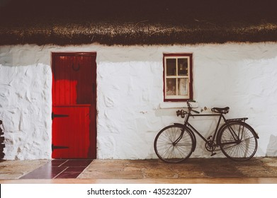 Traditional irish thatched cottage, with red wooden two parts door and an old bicycle. Artistic washed out faded vintage retro edit.
