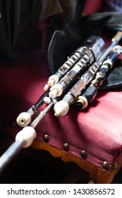 Traditional Irish uilleann pipes (bagpipes) laid out on a vintage pink chair