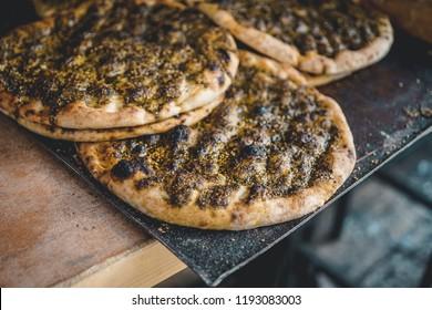 Traditional Israeli flatbread with zaatar close up on a market stall in Jerusalem, Israel. Horizontal food photo