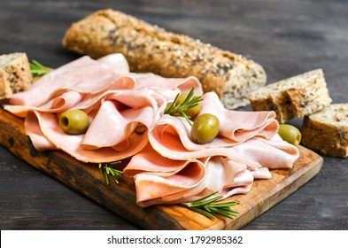 Traditional Italian antipasti mortadella on a wooden plate, served with olives