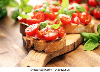 Traditional italian antipasto bruschetta appetizer with cherry tomatoes, cream cheese, basil leaves and balsamic vinegar on wooden cutting board