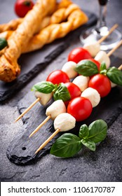Traditional Italian antipasto caprese skewers and grissini bread