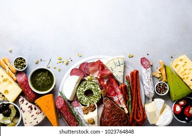 Traditional italian antipasto, cutting board with salami, cold smoked meat, prosciutto, ham, cheeses, olives, capers on grey background. Cheese and meat appetizer. Top view, copy space, flat lay.