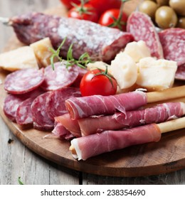 Traditional italian antipasto with prosciutto, cheese, olive and sausage, selective focus