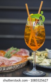 Traditional italian aperitif with proscioutto, mortadella sausage, cheese and aperol spritz drink on the wooden board with blurred food on the background
