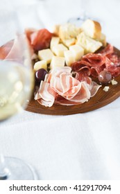 Traditional italian apero: white wine and plate with  prosciutto crudo, salami, parmesan cheese, calamata olives and bread.Selective focus.