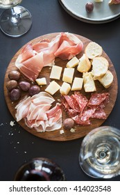Traditional italian apero: white wine and plate with  prosciutto crudo, salami, parmesan cheese, olives and bread. Selective focus.