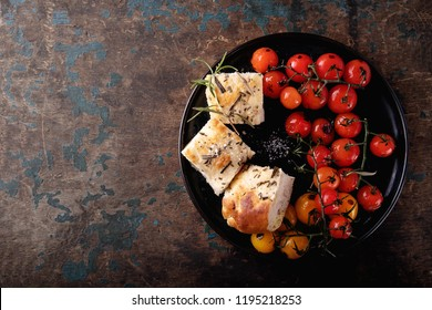 Traditional italian Appetizer home made foccacia bread served with baked tomatoes and rosemary over a rustic wooden background. Top View