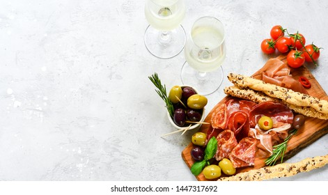 Traditional Italian appetizers ( antipasto ) : salami, bresaola, prosciutto, olives. Aperitif in Italy in Florence, Rome, aperitif in Milan. Two glasses of Prosecco and sticks of cereal bread