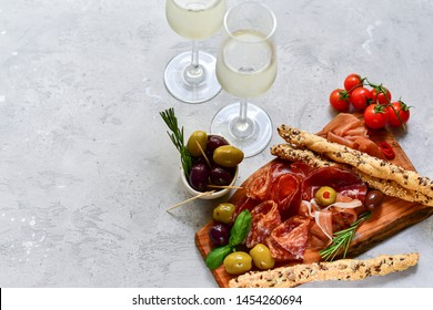 Traditional Italian appetizers ( antipasto ): salami, bresaola, prosciutto, olives. Aperitif in Italy in Florence, Rome, aperitif in Milan. Two glasses of white wine and bread sticks.
