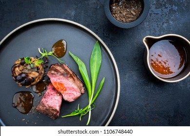 Traditional Italian barbecue aged sliced fillet steak with wild garlic and pioppinos as top view on a plate with copy space