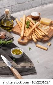 Traditionelle italienische Brotbacken Grissini mit Rosmarin, Parmesan-Käse, Olivenöl, Knoblauch und Salz auf grauem Hintergrund.