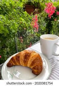 Traditionelles italienisches Frühstück mit süßem Gebäck-Croissant auf Teller und Tasse mit Cappuccino-Kaffee im Sommergarten