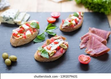 Traditional Italian bruschetta with blue cheese, feta, tomatoes, basil leaves, ham on black stone background.