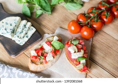 Traditional Italian bruschetta with blue cheese, feta, tomatoes, basil leaves, ham on a wooden background.