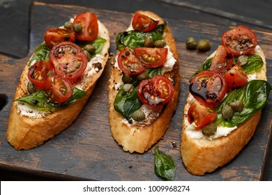 Traditional italian bruschetta with cherry tomatoes, cream cheese, basil leaves, capers and  balsamic vinegar on wooden cutting board. Close up view