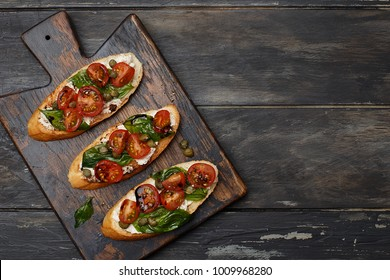 Traditional italian bruschetta with cherry tomatoes, cream cheese, basil leaves, capers and  balsamic vinegar on wooden cutting board. Top view with copy space
