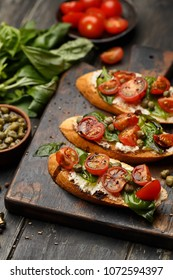 Traditional italian bruschetta with cherry tomatoes, cream cheese, basil leaves, capers and  balsamic vinegar on wooden cutting board. Selective focus