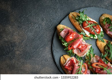 Traditional Italian bruschetta with dried tomatoes, prosciutto and arugula copy space top view.