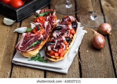 Traditional italian bruschetta with ham and wine