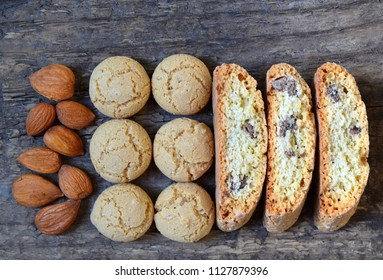 Traditional italian cantuccini and amaretti cookies with almond on old wooden background.Delicious homemade cantucci biscotti and amarettini.Flat lay. Selective focus.