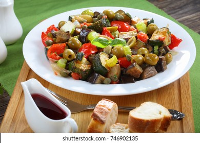 traditional Italian Caponata with aubergine, green olives, capers, celery and herbs on white plate on wooden cutting board with red vine vinegar and bread, view from above, close-up