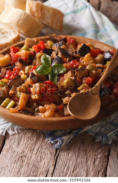 Traditional Italian Caponata with eggplants close-up on a wooden plate. Vertical, rustic style