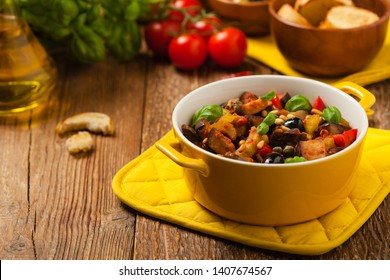 Traditional Italian caponata, served with croutons in a yellow, sunny pot. Decorated with basil and pine nuts. Front view.